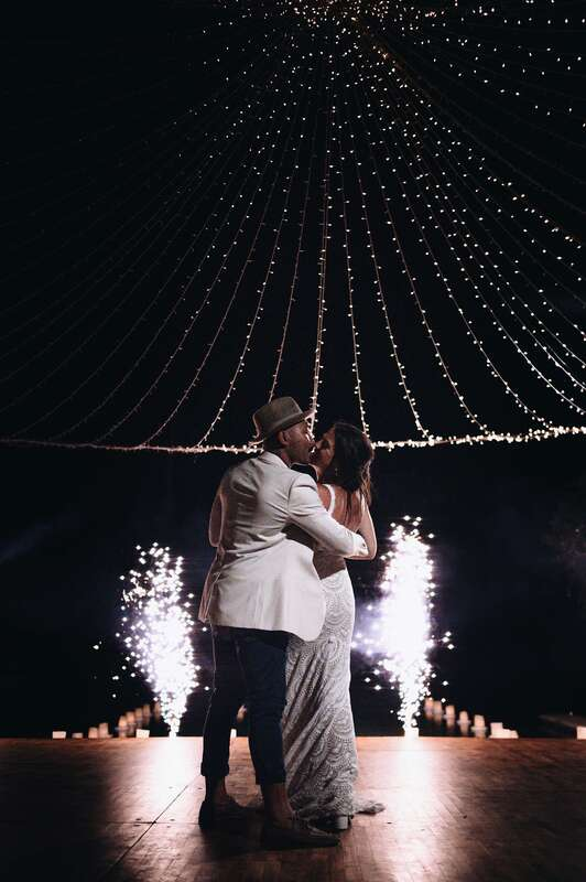Bride and groom kissing under the fairy lights