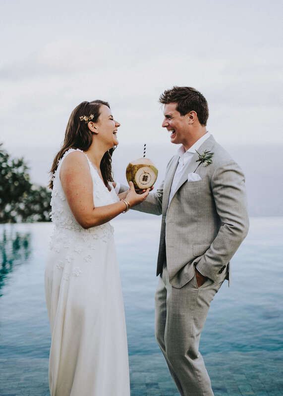 Happy wedding couple holding a coconut
